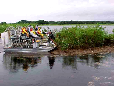 Pushing small floating island away from Highway 60 bridge and flood control structure on Lake Kissimmee (Osceola Co.).