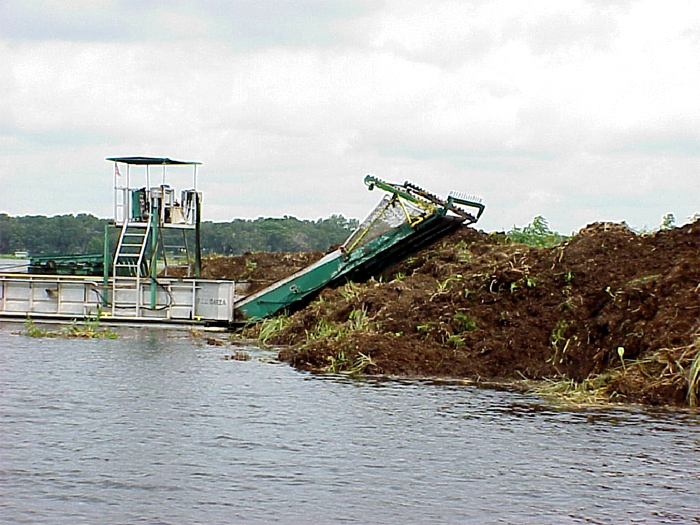 Shredding a floating island in place on Tsala Apopka (Citrus County) using unshredded material as a containment barrier.